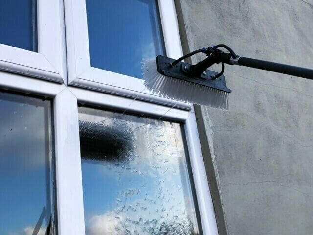 Washing brush putting water on a glass window